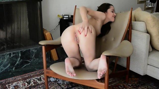 Брюнетка в кресле играется с пизденкой